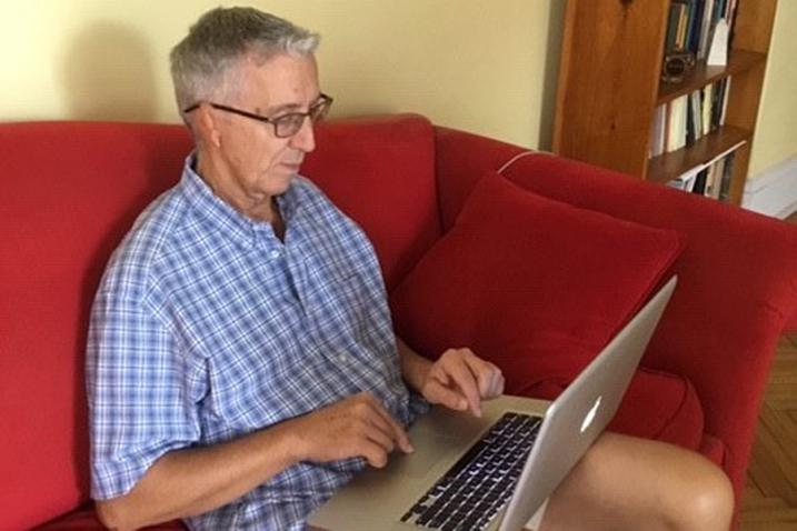 Man sitting in a couch with a laptop on his lap.