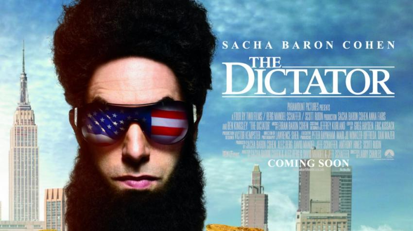 "Movie poster of the actor with heavy beard and sunglasses with reflections of the US flag is on the left side of the picture, with the movie title, ""The Dictator"" on his right."