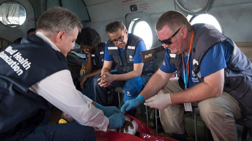 A helicopter transports a wounded health worker and others, while Dr. Michael Ryan helps tend to him.