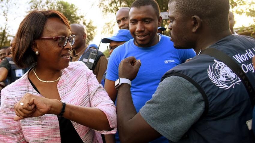 """Dr. Moeti does an elbow shake with a man wearing a vest that says """"WHO"""""""
