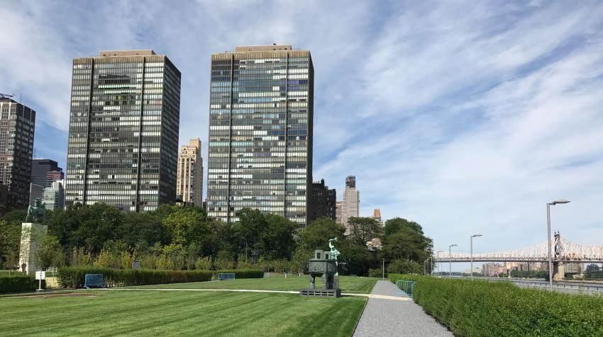 Green area near the East River, with statues from member states and pebbled trail.