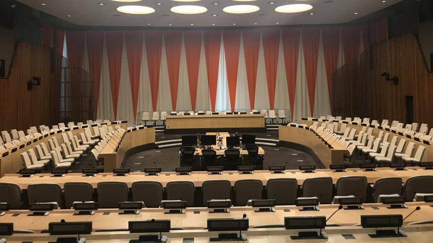 Zoomed in view of the ECOSOC chamber with seats arranged around the room and wall decoration of interchanging red and white triangles.
