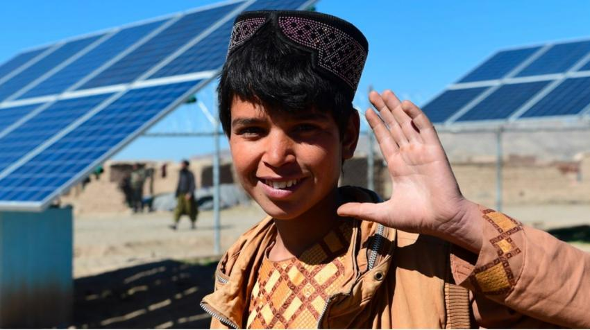 A boy waves in front of solar panels that provide electricity to pump water, in Herat, western Afghanistan.
