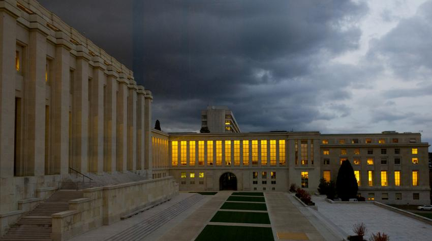 The Palais des Nations at dusk as lights shine out of its windows