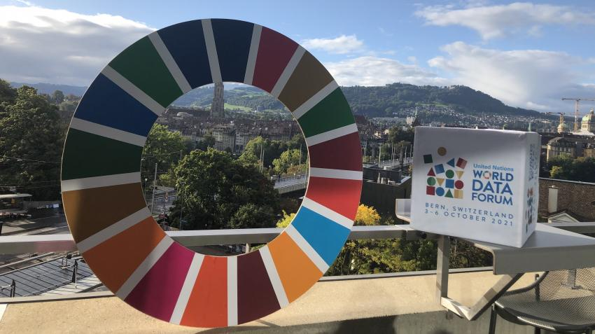 The SDG wheel and UN Data Forum logo are seen overlooking the panorama of Bern