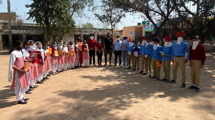Volunteers from Chitkara University (center) pose with students of the government school in Tahu Village in the State of Punjab, India, during a book distribution event, part of the 3R Campaign 2030, 4 March 2021. Photo courtesy of Chitkara University.