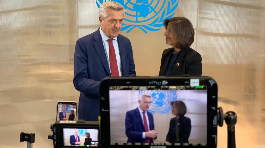 One UN official interviews another in front of the cameras.