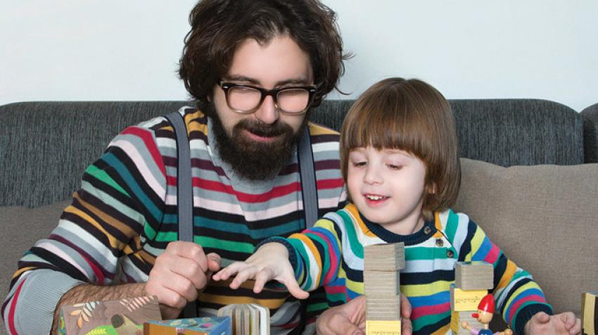 father and young son play with cubes