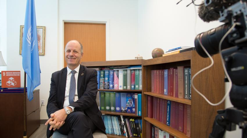 Man sitting on chair in front of book shelf and a UN flag, while being filmed and interviewed.