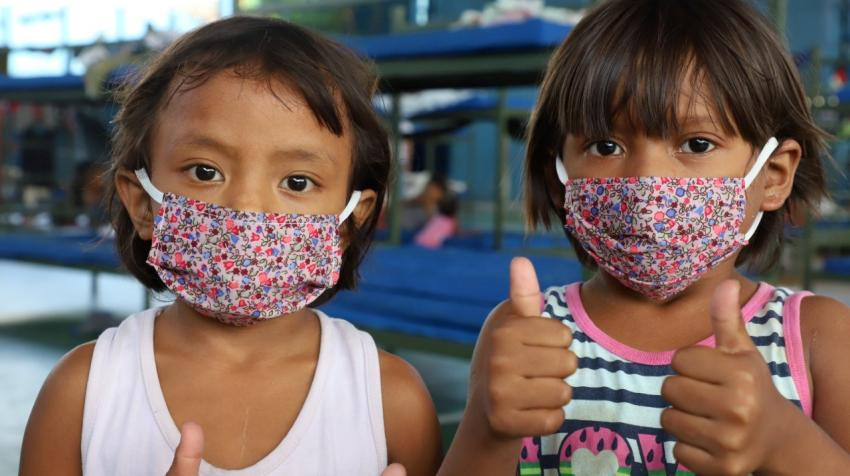 children with masks showing thumbs up