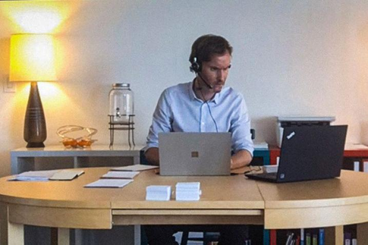 Man with a headset and microphone sits in front of two laptops.