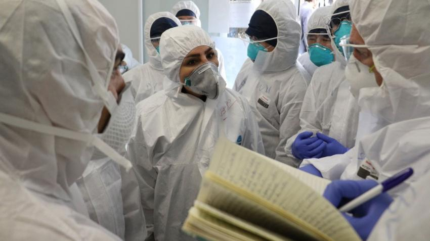 WHO and public health experts are deep in discussion whilst one writes notes. They are dressed in head-to-toe protective gear including face masks.