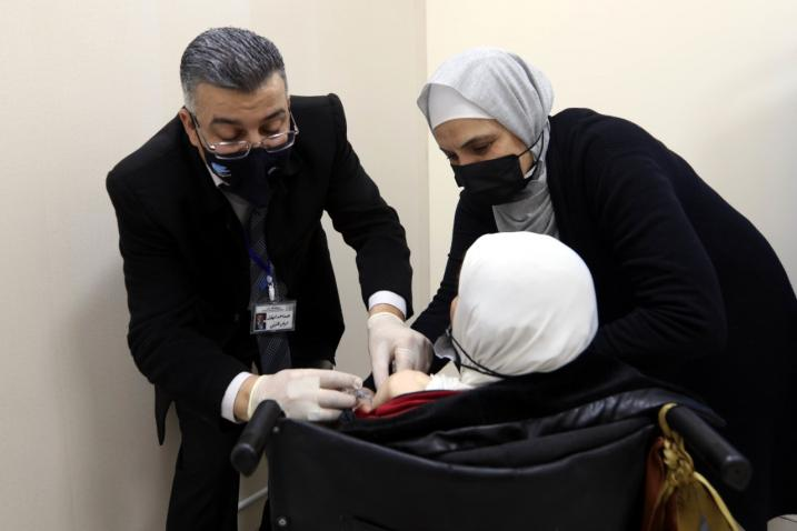 A woman with disability receives COVID-19 vaccine in Amman, Jordan