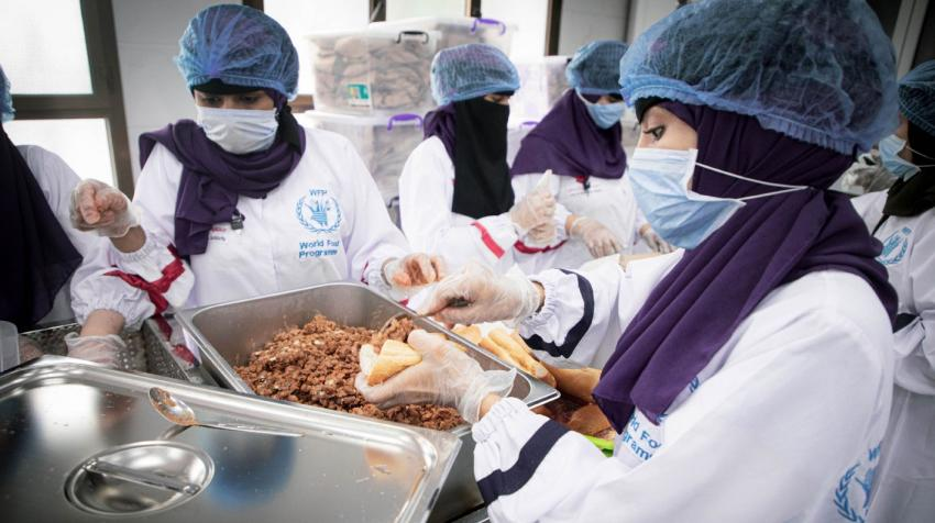 women with masks preparing food