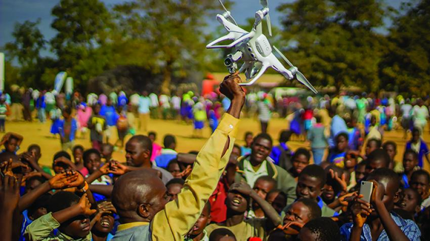 Residents of Kasungu, in central Malawi, gather during a demonstration of unmanned aerial vehicle (drone) technology. The Government of Malawi and UNICEF are testing the use of drones for humanitarian purposes. 28 June 2017. © UNICEF/UN070228/Chisiza