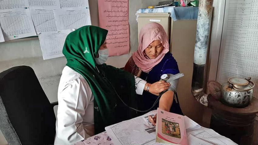 A midwife takes a woman's blood pressure at a family health house in rural Afghanistan.