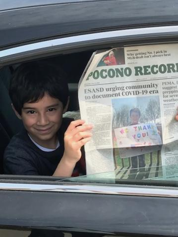 Jayden, a student at Bushkill Elementary, holds up a copy of the Pocono Record, featuring a picture of him with his sign supporting essential workers.