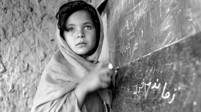 A young Afghan girl writes on chalkboard