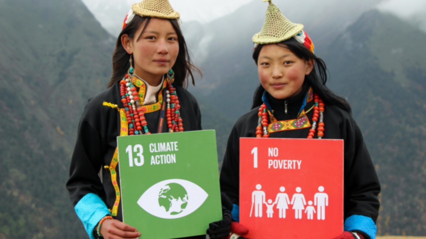two girls holding up Climate Action and No Poverty cards