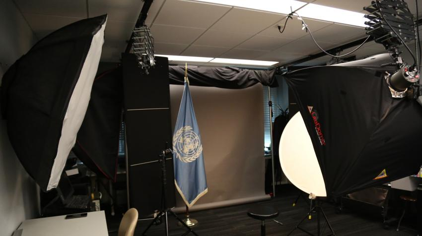 Entrance view of a studio with lighting equipment, a UN flag, and a set of different background screens.