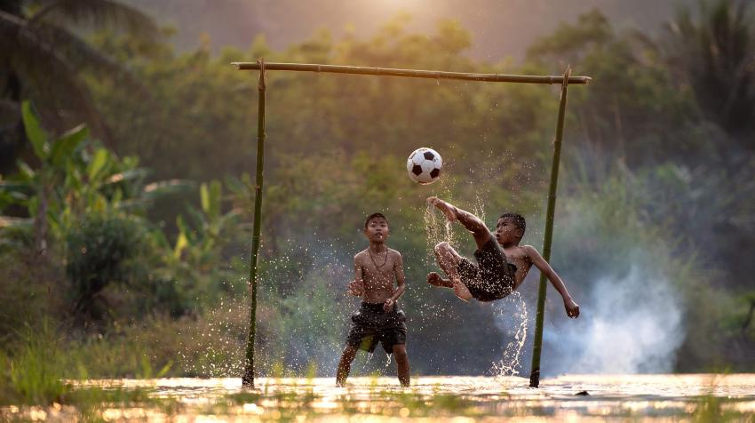 Boys playing football (soccer). Photo by VietNam Beautiful on Unsplash