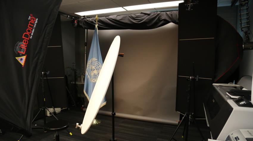 View of the photo studio from the right, with lighting, UN Flag, reflector, and background screen.
