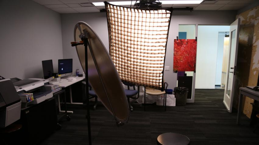 View of studio from the opposite side of the entrance, showing lighting equipment, reflector, computers, and printers.