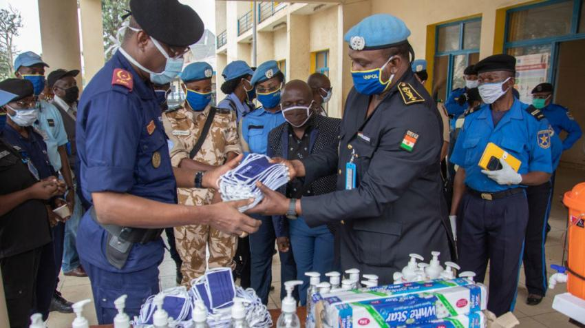 police handing over face masks and hand sanitizer