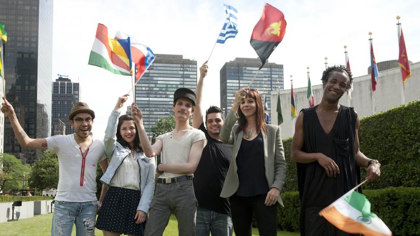 Participants of Project Runway standing at the lawn of the UN Headquarters with the world flags.