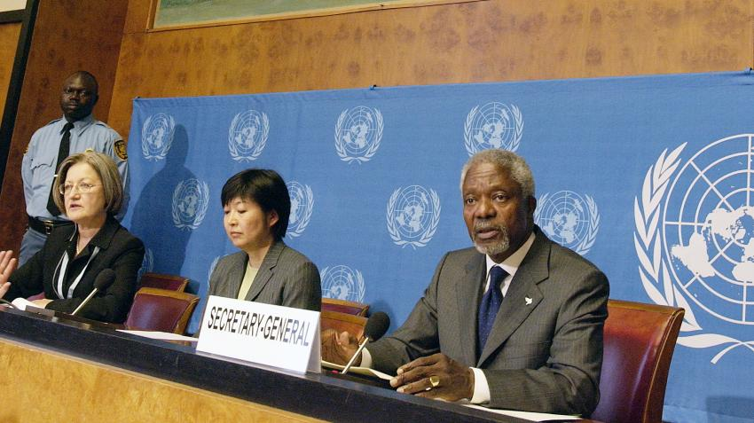 View of Secretary-General Kofi Annan speaking, next to two women, at wooden main desk in front of blue background with UN emblem.