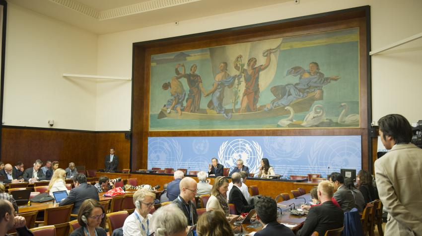 View of artwork at end of Room 3 above UN personnel speaking to press