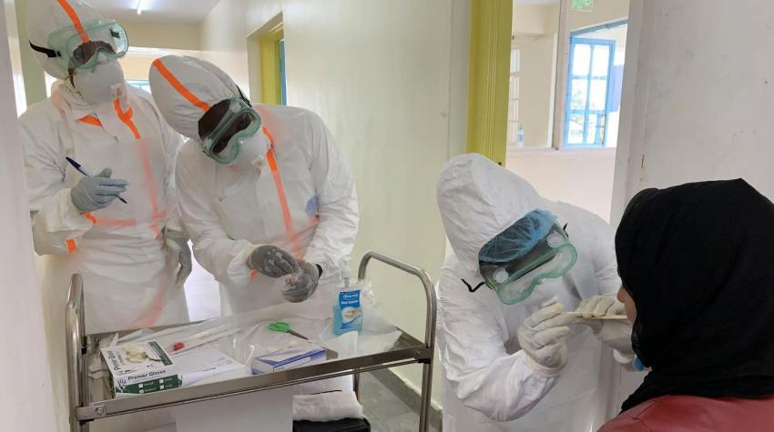 medical team in protective gear getting test sample