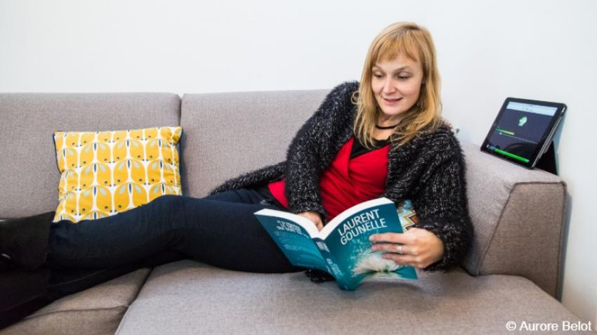 A woman reclines on a sofa and reads from a book.