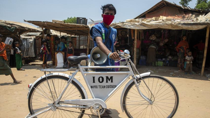 A cyclist with megaphone at a refugee camp