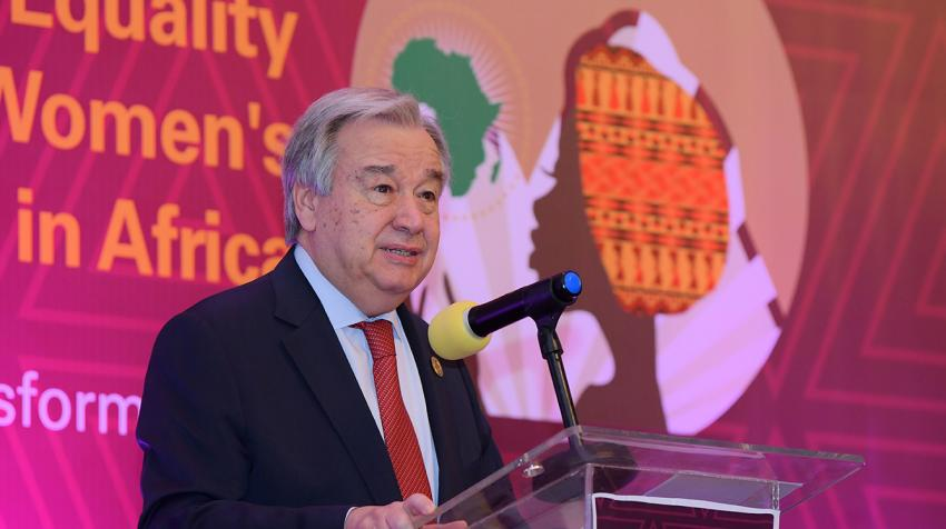 Secretary-General António Guterres at a podium with poster on African women's empowerment behind him