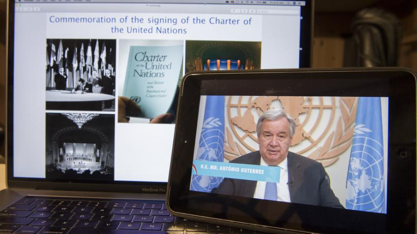 Secretary-General António Guterres on screen in front of bigger screen with UN Charter photos