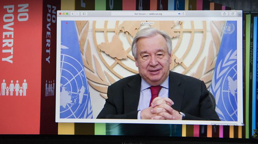 Secretary-General António Guterres on screen with background of SDGs