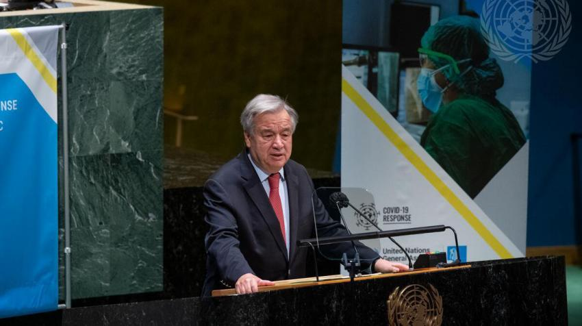 Secretary-General António Guterres at a podium with COVID-19 poster