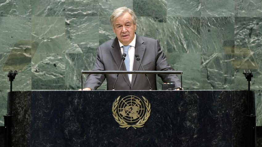 The Secretary-General speaking at a black marble podium with a golden UN emblem.