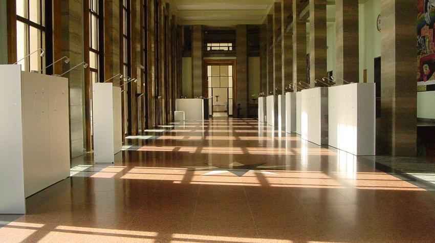 Long hallway with brick-colored floor with brown pillars on both sides of the hallway.