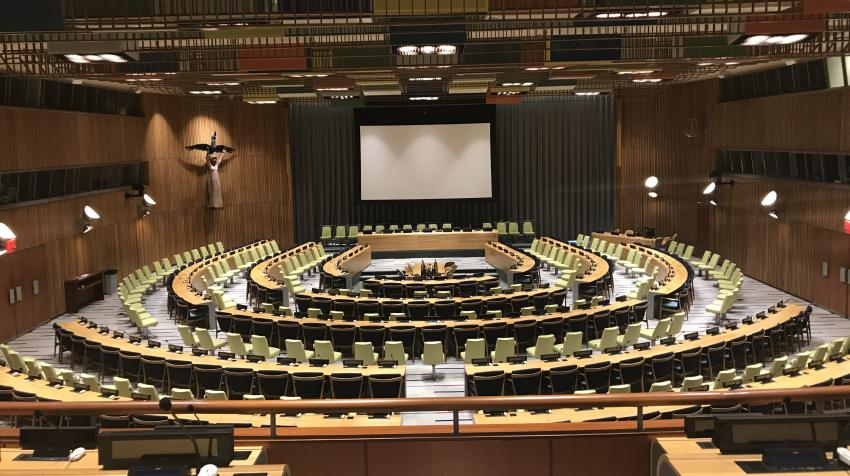 General view of the Trusteeship Council from the third floor, with chairs arranged around the room and a projector screen on the front wall of the chamber.