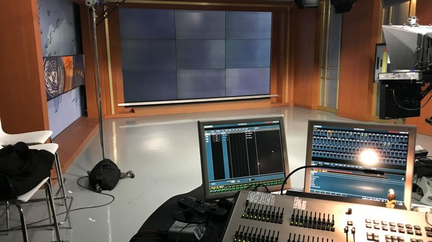 View of the TV studio with a mixing console in front of a news set.