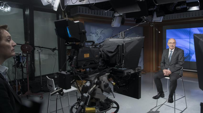 A man sitting on a chair in the TV set with cameras filming him.