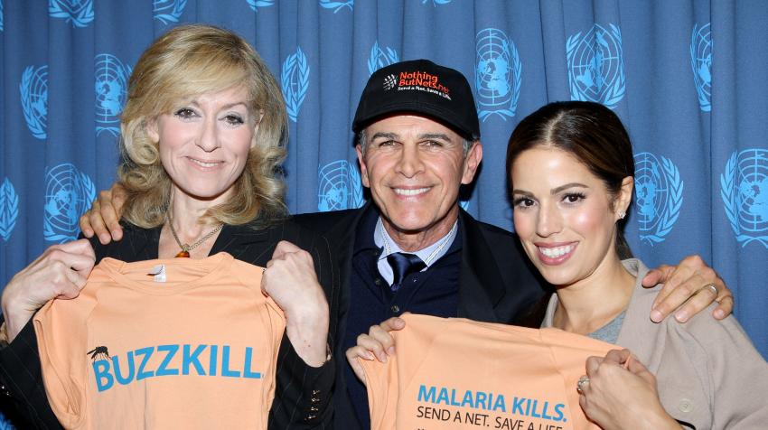"Two women and one man holding orange t-shirts saying ""Malaria Kills. Send a net. Save a light."""