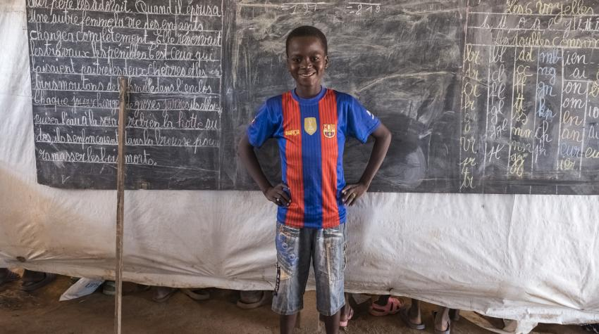 A young boy stands in front of the blackboard in a classroom at the peacekeeping site in Kago Bandoro, Central African Republic,