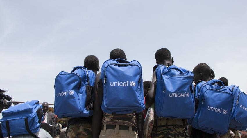 Children released from armed groups are in a circle, with blue UNICEF backpacks.