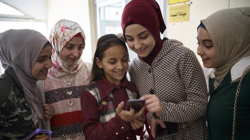 Syrian children use a smart phone outside a Technology Room designed to provide children with a creative learning experience at New Damietta Primary Health Centre in Damietta Governorate, Egypt, 2017. ©UNICEF/UN0212339/Shehzad Noorani