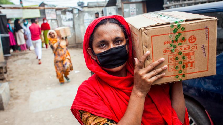 women wearing facemasks carry boxes on their shoulders
