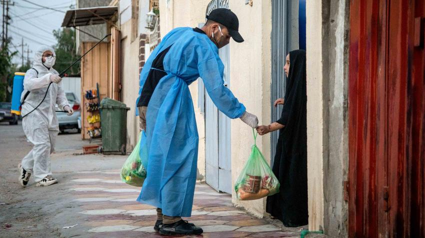 A volunteer provides food to a child in a residential neighbourhood