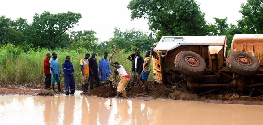A group of truck drivers take turns clearing earth to drain water from an impassable section of road and an overturned truck is behind them.